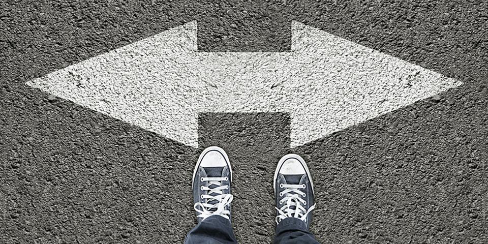 En persons fødder som står overfor to pile i hver sin retning