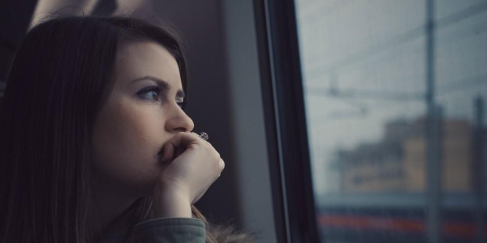 Ung kvinde kigger ud af togvindue