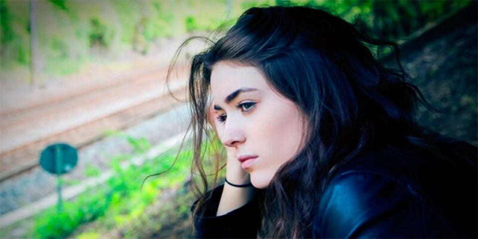 ung kvinde kigger eftertænksomt ud af vinduet